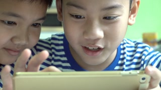 Young happy asian two boy playing game with cellphone and tablet computer .