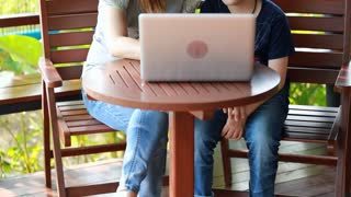 Young, happy mother with child using laptop on terrace