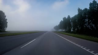 car moves on the road to heavy fog