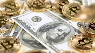 Gold Bit Coin BTC coins and dollar bills.