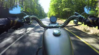 Riding a motorcycle. Biker rides on the road with a first-person.