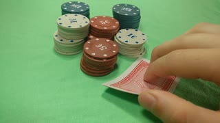 Poker player checks his cards and places a bet. Two aces close up.