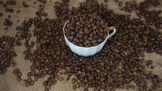 Roasted coffee beans poured into the coffee cup