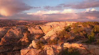 A aerial shot of beautiful desert cliffs and sunset landscape