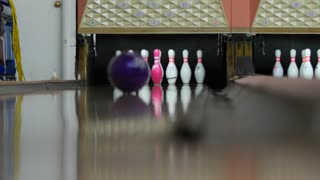 A ball hits pins in bowling alley