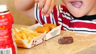 A boy eats chicken nuggets and french fries with chocolate milk