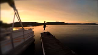 A boy fishing with a pole off a dock at sunse