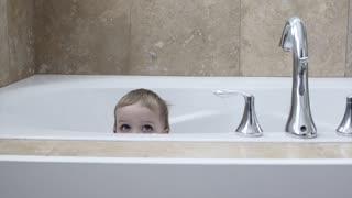 A boy playing in the bath tub