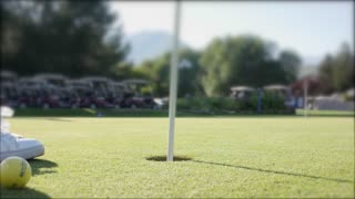 A boy practicing putting at a golf course