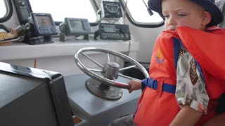 A boy steering a fishing boat of coast of Cape Breton