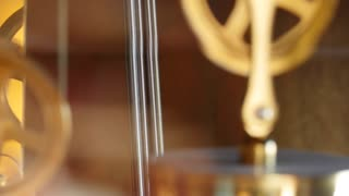 A closeup slow dolly shot of pendulum on grandfather clock