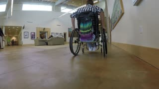 A college student in wheel chair moving down a hallway