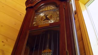 A cool old grandfather clock in living room tilting shot