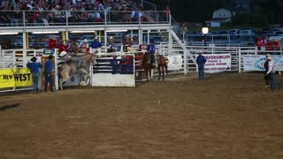 a cowboy bronc ride in rodeo slow motion