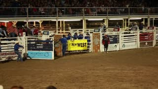a cowboy riding a big bull at rodeo slow motion