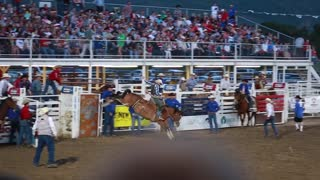 a cowboy riding a bronc at rodeo slow motion