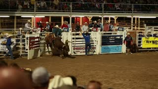 a cowboy riding big bull at rodeo slow motion