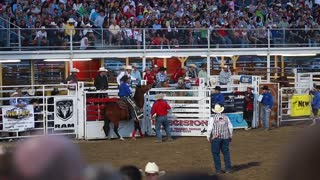 a cowboy riding bronc at rodeo slow motion