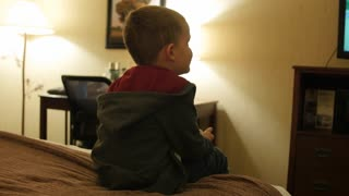 A Cute Little Boy Watching Tv In Hotel Room At Night