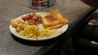 A Dolly Shot Of A Man Eating Bacon Eggs And French Toast