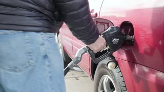 A Dolly Shot Of A Man Filling Up The Car With Gas