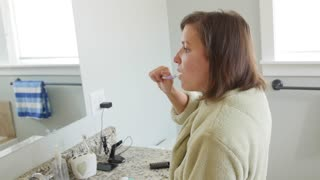 A dolly shot of a woman brushing her teeth in robe