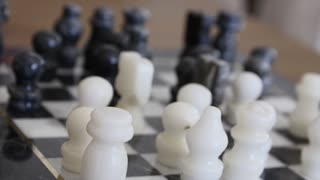 A dolly shot of chess pieces on the stone chess board