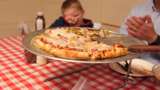 A Dolly Shot Of Family Eating Pizza In A Pizzeria
