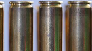 A Dolly shot of large caliber bullets in a production line