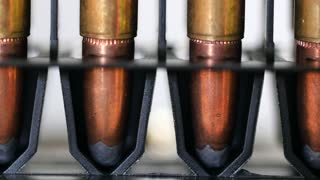 A Dolly shot of large caliber bullets in production line
