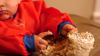 A dolly shot of messy baby boy eating his birthday cake at home