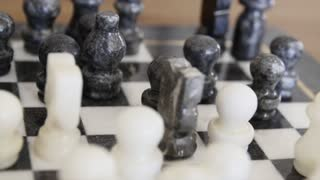 A dolly shot of stone chess pieces on chess board