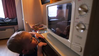 A family cooking frozen pizza in hotel microwave