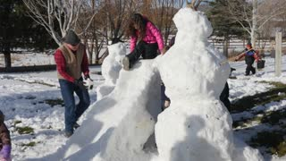 A family makes snow men and a slide from snow