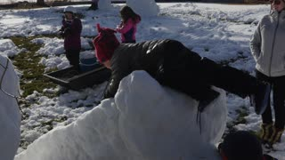 A family making snow men and a slide from the snow
