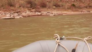 a family rowing a river through a deep desert canyon timelapse