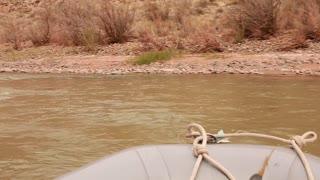 a family rowing a river through a deep desert canyon