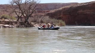 a family rowing down a desert canyon river in rafts