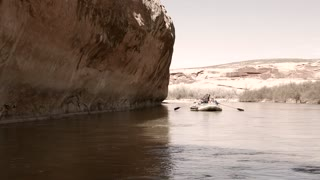 a family rowing river rafts down the san juan river by cliff