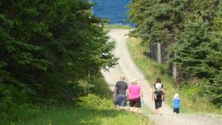 A family walking through trees toward beach