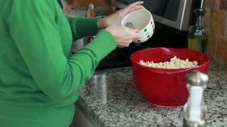 a female adding salt and butter to popcorn