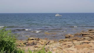 a fishing boat off a rocky shoreline