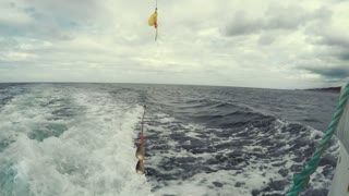 A fishing lure hanging off of a fishing boat in ocean