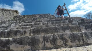 A gimbal shot of woman hiking up mayan ruins at ek balam