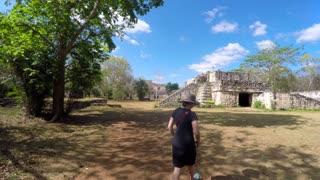 A gimbal shot of woman walking through mayan ruins at ek balam