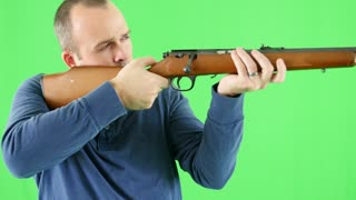 A green screen shot of a shooter with a rifle at camera