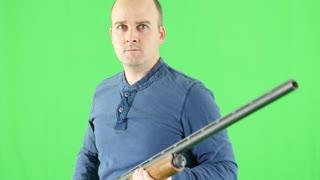 A green screen shot of a shooter with his shotgun at camera