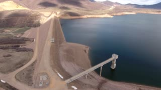 A high aerial shot of a mountain reservoir and dam