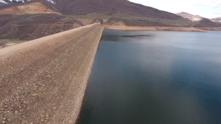 A high aerial shot of low mountain reservoir and dam
