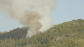 A huge mountain wildfire with smoke on summer day